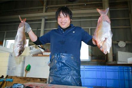 両手に魚を持つ作業員